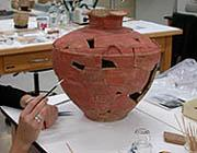 Conservator cleaning ceramic vessel