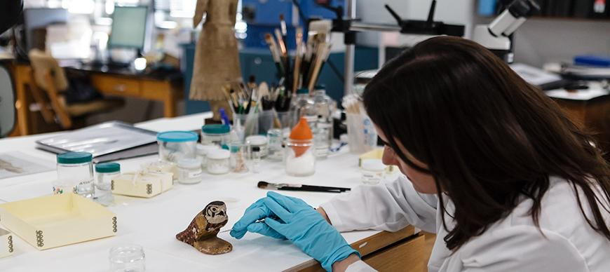 Conservator Alison Whyte prepares OIM E972, wood bird statue for an exhibition