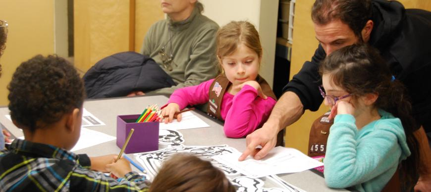 Image: Girl Scouts work with a parent to learn about the major bones of the human skeleton.