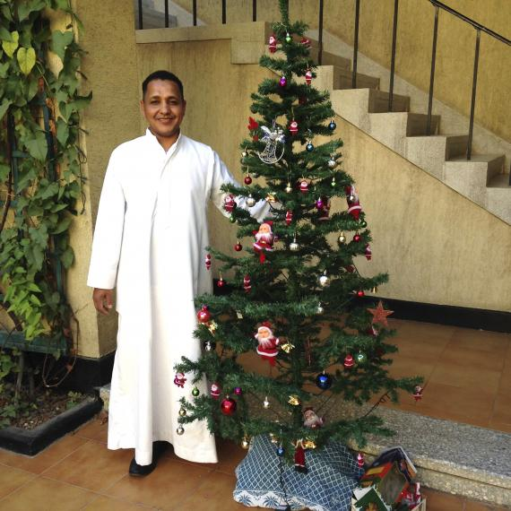 Chicago House kitchen assistant Zakaria Mohammed with Christmas tree.  Photo by Ray Johnson