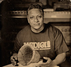 Mario Silva, a baker at the Medici Bakery on 57th Street is shown with an Egyptian bread pan from about 2630–2524 BC. OIM E1986